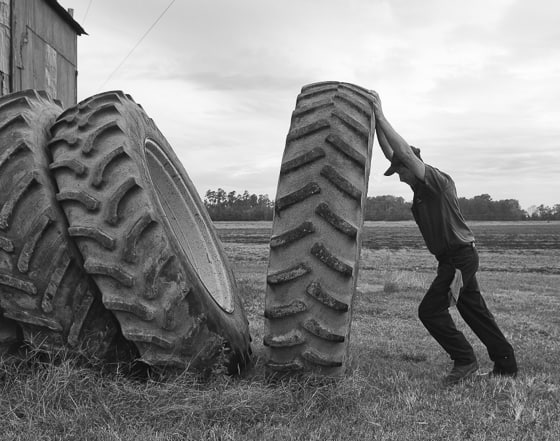 """Tires wear out on tractors too. Josh Riley returns a tire to the """"used"""" inventory."""